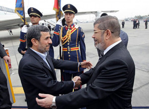 Then Egyptian President Mohamed Morsi embraces then Iranian President Mahmoud Ahmadinejad upon his arrival in Cairo on February 5, 2013.