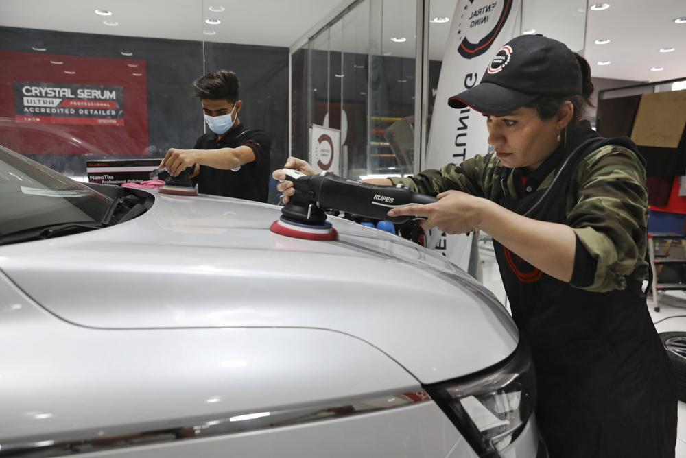 At Tehran garage, Iranian woman polishes cars and her dreams